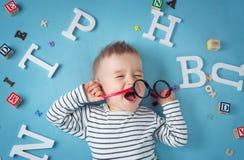 Один годовалый ребенок лежа с зрелищами и письмами стоковое фото rf