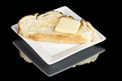 Один кусок хлеба и Пэт масла на белой плите Стоковая Фотография