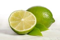 Один лимон с половиной сочной известки на деревянном столе Стоковое Изображение RF