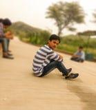 Один мальчик сидя на дороге Стоковое Фото