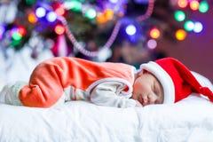 Один младенец недели старый newborn в шляпе Санты около рождественской елки Стоковое фото RF