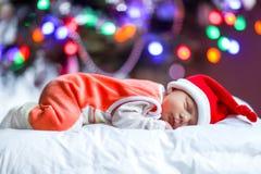 Один младенец недели старый newborn в шляпе Санты около рождественской елки Стоковые Фото