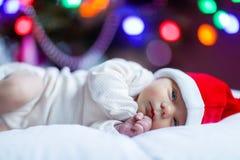 Один младенец недели старый newborn в шляпе Санты около рождественской елки Стоковые Изображения