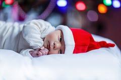 Один младенец недели старый newborn в шляпе Санты около рождественской елки Стоковое Изображение RF