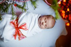 Один младенец недели старый newborn обернутый в одеяле около рождественской елки Стоковые Изображения