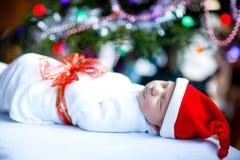 Один младенец недели старый newborn обернутый в одеяле около рождественской елки Стоковое фото RF