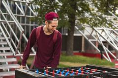 Один молодой человек в вскользь одеждах играя foosball в общественном парке концепция игр таблицы стоковые фото