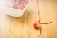 Один сладкая вишня и шар со сладкими вишнями на деревянной предпосылке/одной сладкой вишне и шар со сладкими вишнями на деревянно стоковые изображения