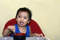 Один 1-ти летний ребёнок уча съесть самостоятельно усмехаться счастливый но грязный Стоковые Изображения RF
