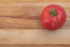 Один томат на разделочной доске Стоковая Фотография RF