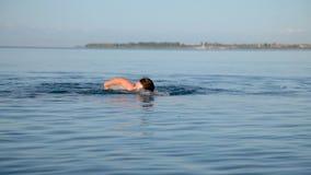 Один человек плавает в озере в раннем утре сток-видео