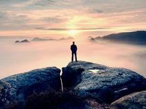 Один hiker в красной стойке крышки на пике утеса песчаника в империях утеса паркует и наблюдающ над туманом Стоковая Фотография