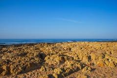 Одичалый пляж океана лета, Португалия Ясное небо, утесы на песке Стоковая Фотография RF