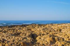 Одичалый пляж океана лета, Португалия Ясное небо, утесы на песке Стоковое фото RF
