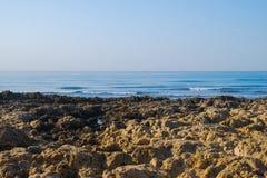 Одичалый пляж океана лета, Португалия Ясное небо, утесы на песке Стоковые Фото