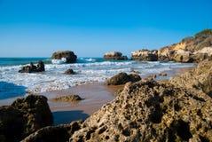Одичалый пляж океана лета, Португалия Ясное небо, утесы на песке Стоковое Изображение