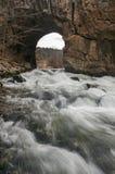 Одичалый поток свежей воды приходя через естественный тоннель воды стоковая фотография