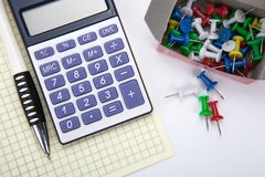 Одна большие калькулятор и канцелярские принадлежности на белой таблице стоковое изображение