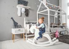Одна годовалая девушка играя близко в комнате с лошадью игрушки, ska Стоковые Фотографии RF