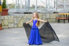 Одна красивая маленькая девочка приспосабливает современного танцора в голубом костюме, молодом танцоре, танцуя и скача, танец с  стоковые изображения rf