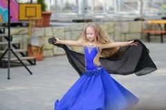 Одна красивая маленькая девочка приспосабливает современного танцора в голубом костюме, молодом танцоре, танцуя и скача, танец с  стоковое фото rf