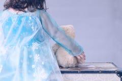Одна маленькая девочка одетая как принцесса держит плюшевый медвежонка пока сидящ на комоде стоковая фотография rf