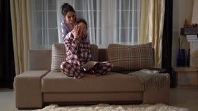 Одна милая двойная сестра игриво закрывая глаза с руками других, когда она журнал чтения на уютной живущей комнате акции видеоматериалы