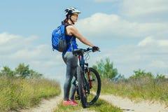 Одна молодая женщина едет на горном велосипеде вне городка на дороге в лесе Стоковое Фото