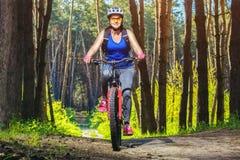 Одна молодая женщина едет на горном велосипеде в лесе Стоковые Фото