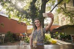 Одна молодая красивая девушка себя принимая снимок, фотографируя, selfie, в саде кафа на открытом воздухе, используя смартфон стоковые изображения