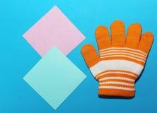 Одна перчатка ` s детей оранжевая с белыми нашивками лежит на голубой поверхности, splayed пальцах, способности греть ваши руки в стоковые изображения rf