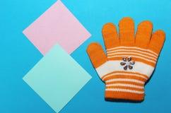 Одна перчатка ` s детей оранжевая с белыми нашивками лежит на голубой поверхности, splayed пальцах, способности греть ваши руки в стоковое изображение