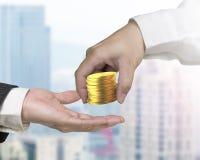 Одна рука давая стог золотых монеток к другим Стоковое фото RF