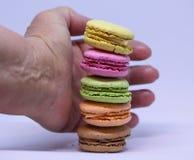 Одна рука ` s принимая красочные macarons Стоковая Фотография RF