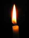 Одна светлая свеча горя ярко в черной предпосылке Стоковая Фотография RF