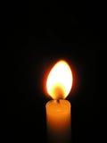 Одна светлая свеча горя ярко в черной предпосылке Стоковые Фото