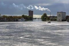 Одна шлюпка на реке в солнечном свете в дне с промышленным paysage Стоковое Фото