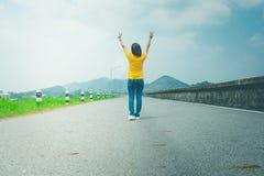 Одни путешественник или backpacker женщины идя вдоль дороги сельской местности вдоль стороны с резервуаром, она поднимает руки на стоковые изображения