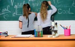 Одноклассники девушек изучают химию Микроскоп и пробирки на таблице химические реакции Make изучая химию стоковые фотографии rf