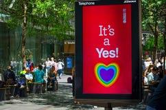 Однополый брак совету Сиднея поддерживая с радугой сердца на мониторе экрана говорит ` оно ` s утвердительный ответ! знамена ` стоковые изображения