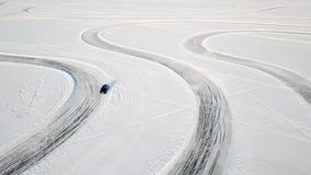 Одно вождение автомобиля через лес зимы на проселочной дороге Взгляд сверху от трутня Вид с воздуха снега покрыл дорогу внутри Стоковое Изображение