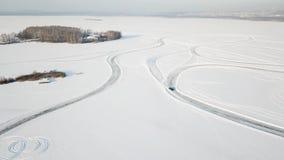 Одно вождение автомобиля через лес зимы на проселочной дороге Взгляд сверху от трутня Вид с воздуха снега покрыл дорогу внутри Стоковые Изображения RF