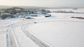 Одно вождение автомобиля через лес зимы на проселочной дороге Взгляд сверху от трутня Вид с воздуха снега покрыл дорогу внутри Стоковое фото RF