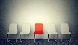 Одно раскрывая для концепции работы Строка белых стульев и одного красного цвета в середине Стоковая Фотография