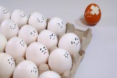 Одно яичко другого цвета между всеми белыми яичками Стоковые Изображения RF