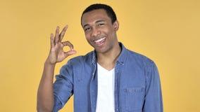 Одобряйте знак молодым африканским человеком, желтой предпосылкой