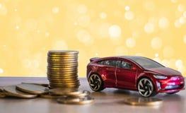 Одолжите концепции финансов, автомобиль игрушки и монетки на золотом светлом bokeh b Стоковые Фотографии RF