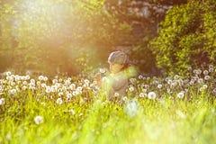 Одуванчик маленькой курчавой девушки дуя в парке стоковые фотографии rf