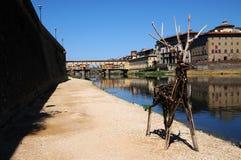 15-ое августа 2017: Деревянные животные около River Arno с известным старым мостом на заднем плане Флоренция Стоковое фото RF