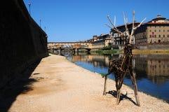15-ое августа 2017: Деревянные животные около River Arno с известным старым мостом на заднем плане Флоренция Стоковые Изображения